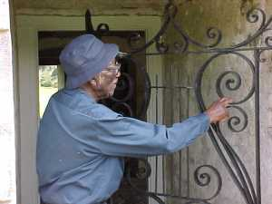 Mr. Simmons points to areas he repaired on Drayton Hall's wrought iron harp gate.