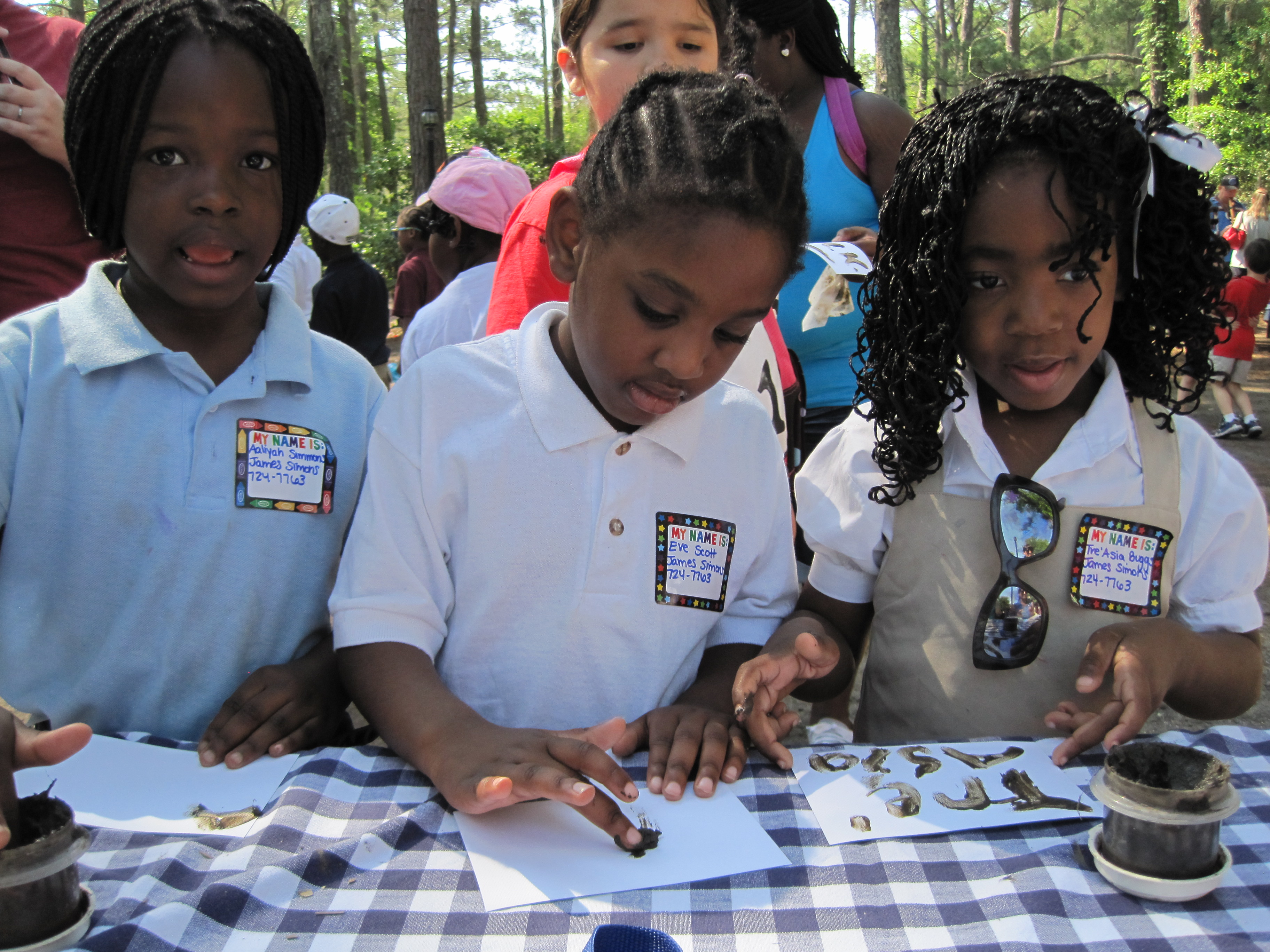Children at the Drayton Hall table experiment with pluff mud drawings!