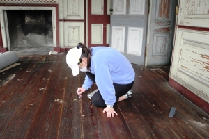 Tara cleaning the floor boards in the small yellow room on the first floor.