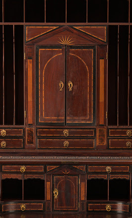 Shielded behind the paneled mirror and fall-front of Drayton Hall's desk and bookcase is an architecturally-inspired interior fabricated with exotic woods from around the globe, tortoise-shell inlay, and gilt brass hardware.  A series of 28 delicate drawers, a locking cabinet at the center of the bookcase, and a prospect below, form a balanced appearance and conceal 13 secret compartments.